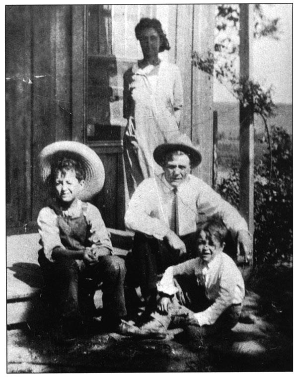 Woody (izquierda), su hermano George y sus padres en el porche de la casa de Okemah