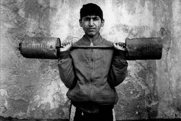 Muchacho gitano posando con pesas de cemento en Belgrado (Boogie, 1996)