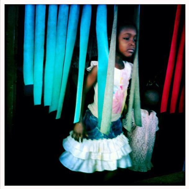 Una niña en el puesto de venta de sus padres en Duekoue, Costa de Marfil, 7 de marzo de 2012 (Instagram de Peter DiCampo)
