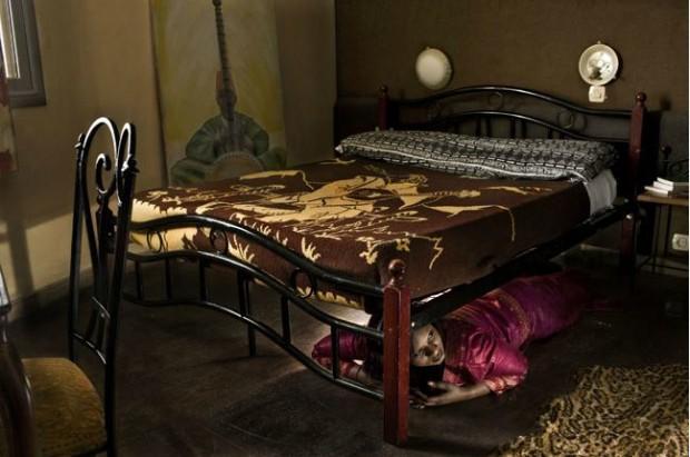 Sandrine Nzi, hija y heredera del dueño de varias minas de oro, escondida bajo la cama de un modesto hotel para que su familia no la mate- ('Poly- Spam'. Cristina de Middel)