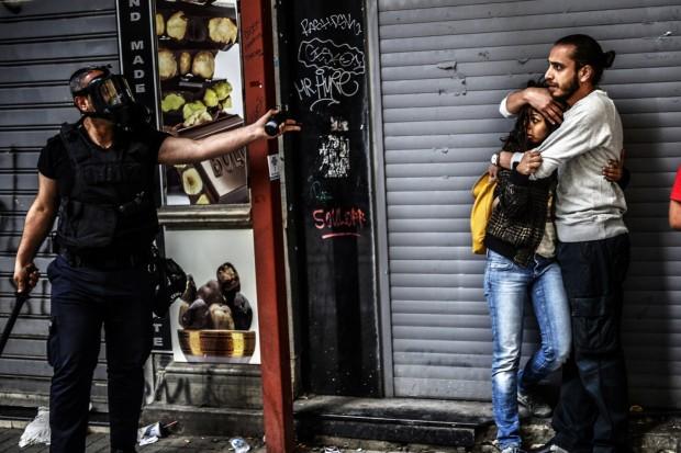 Estambul (Turquía), 31 de mayo. Un policía amenaza a una pareja durante las manifestaciones en favor de mayores libertades ciudadanas © Bulent Kilic / AFP