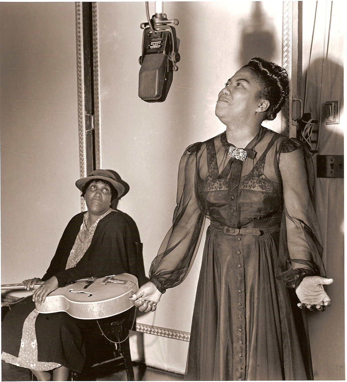 Sister Rosetta canta y su madre, Katie Bell, sostiene la guitarra. Foto: Charles Peterson