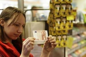 Una cajera observa un billete de 10 euros en un supermercado en Riga (Letonia).  (EFE / Archivo)