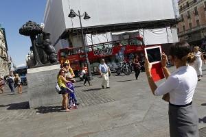 Un grupo de turistas se fotografía en el Oso y el Madroño de la madrileña Puerta del Sol. (Jorge París)