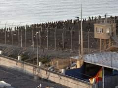 Un grupo de inmigrantes junto a la valla fronteriza de separación en Ceuta. EFE)