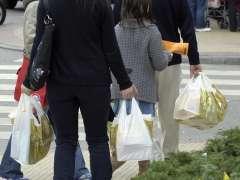 Personas con las clásicas bolsas de plástico de comercios. (ARCHIVO)