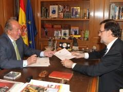 El rey Juan Carlos firmando el documento de su abdicación. (EFE)