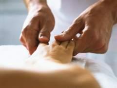 Un fisioterapeuta practicando un masaje a una mujer. (GTRES)