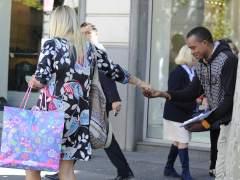 Una mujer da limosna a una persona en Madrid (GTRES)