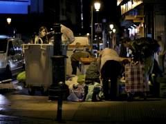 Un grupo de personas rebusca en un contenedor de basura. (GTRES)