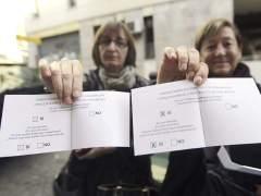 Dos mujeres enseñan sus papeletas del proceso participativo del 9-N en Cataluña. (EFE)