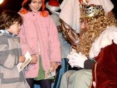 Dos niños entregan su carta a uno de los Reyes Magos. (EFE)