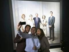 Tres periodistas se hacen un selfie ante el cuadro La Familia de Juan Carlos I, de Antonio López (EFE)