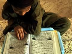 Un niño lee el Corán en una mezquita de Karachi, en Pakistán. (EFE)