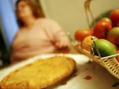 Una mujer obesa ante una mesa con varios alimentos. (ARCHIVO)