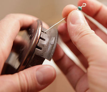 Usa un alfiler o aguja finos para desatascar los orificios de los quemadores de gas